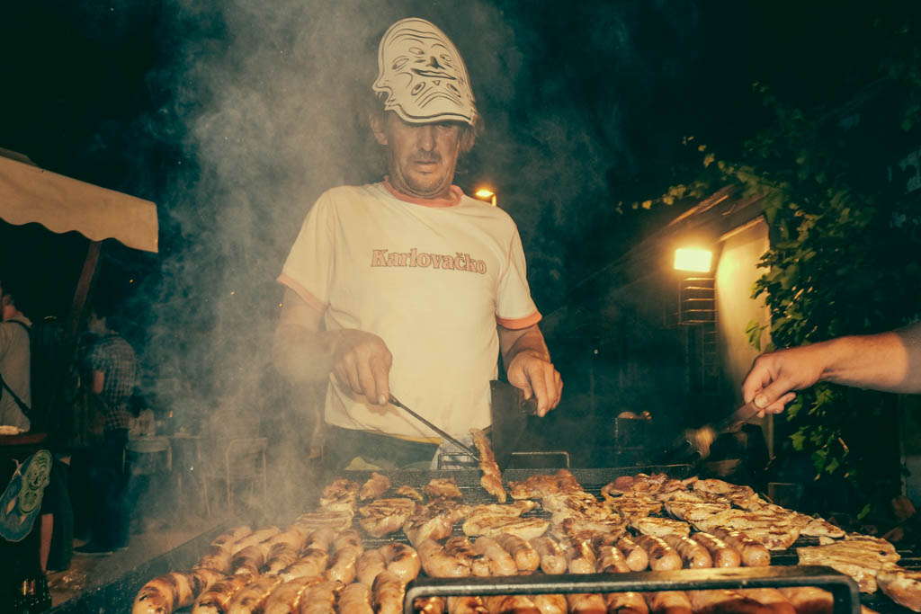 Shipyard worker cooking the BBQ for art freaks and fans. Skver, Mali Losinj.