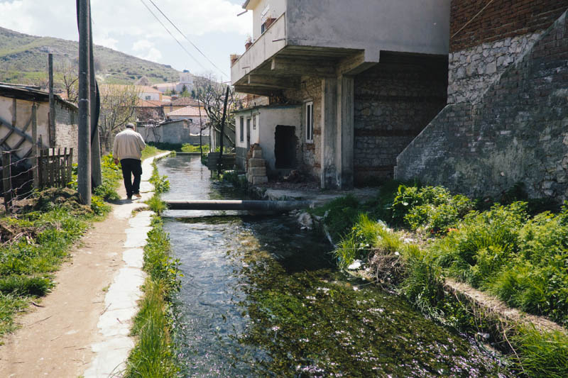Petrit walking into Tushemisht village, Albania. The canals are filled with natural spring water.